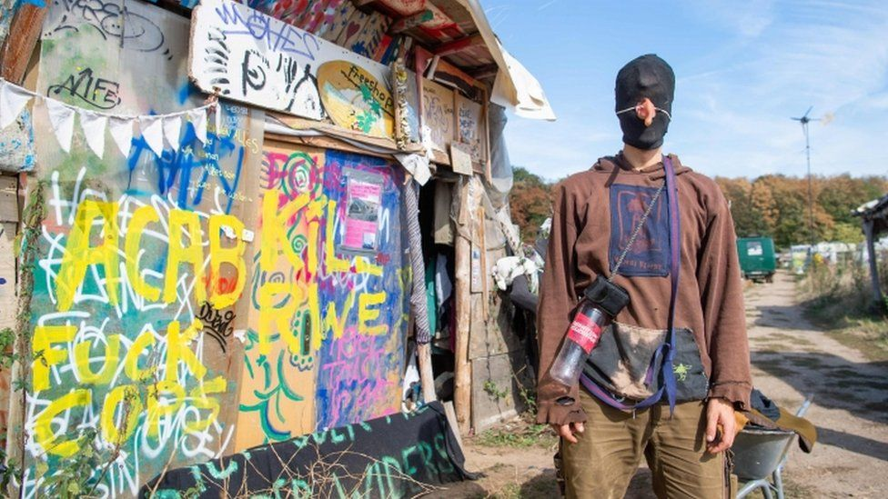 A hooded environmentalist stands at a camp the Tagebau Hambach mine in Kerpen, western Germany.