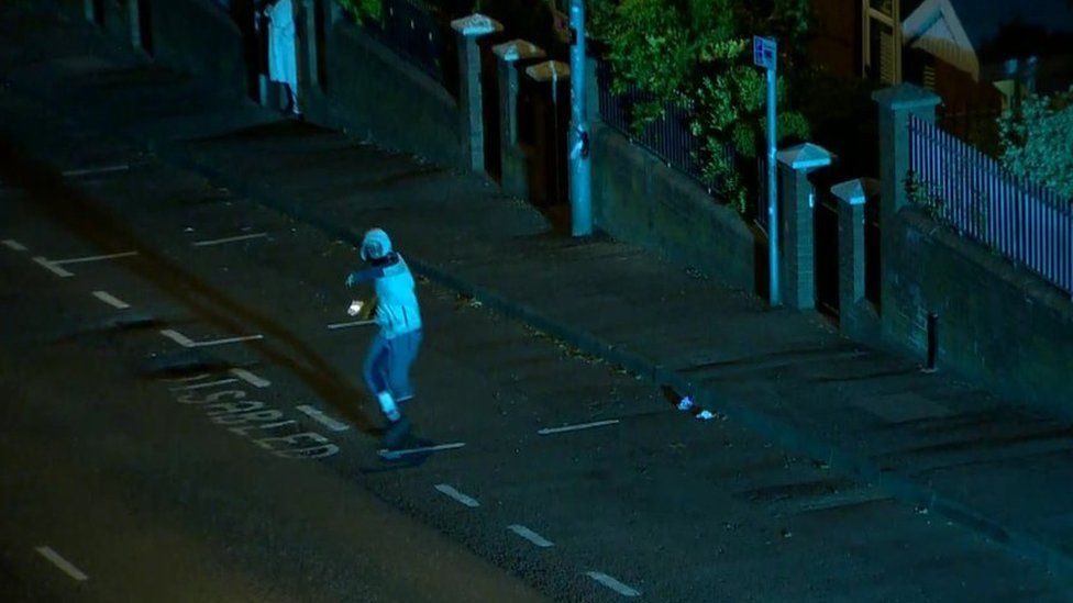 A rioter throws a petrol bomb