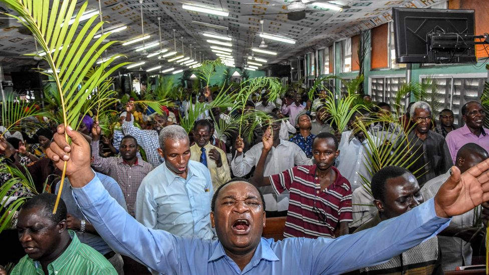 People holding palm leaves in a church in Dar es Salaam, Tanzania - Sunday 5 April 2020