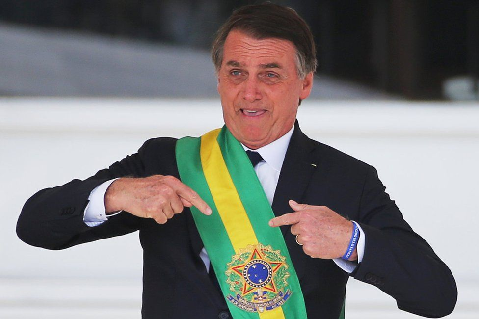 Jair Bolsonaro gestures after receiving the presidential sash from outgoing President Michel Temer at the Planalto Palace, in Brasilia, Brazil January 1, 2019