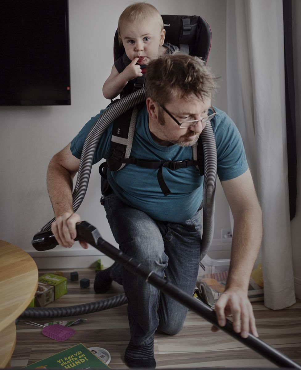 Man vacuuming with his son on his back