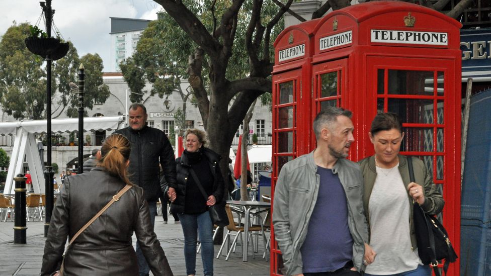 People in Gibraltar walk past a red phone box