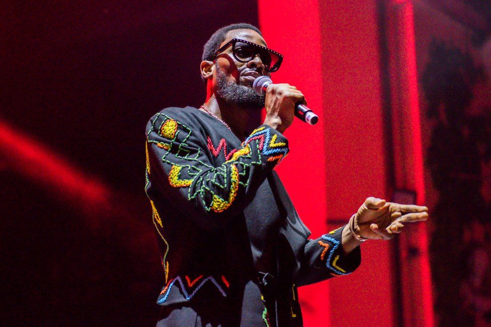 D'banj stands on stage with a microphone, wearing a colourful embroidered blazer.
