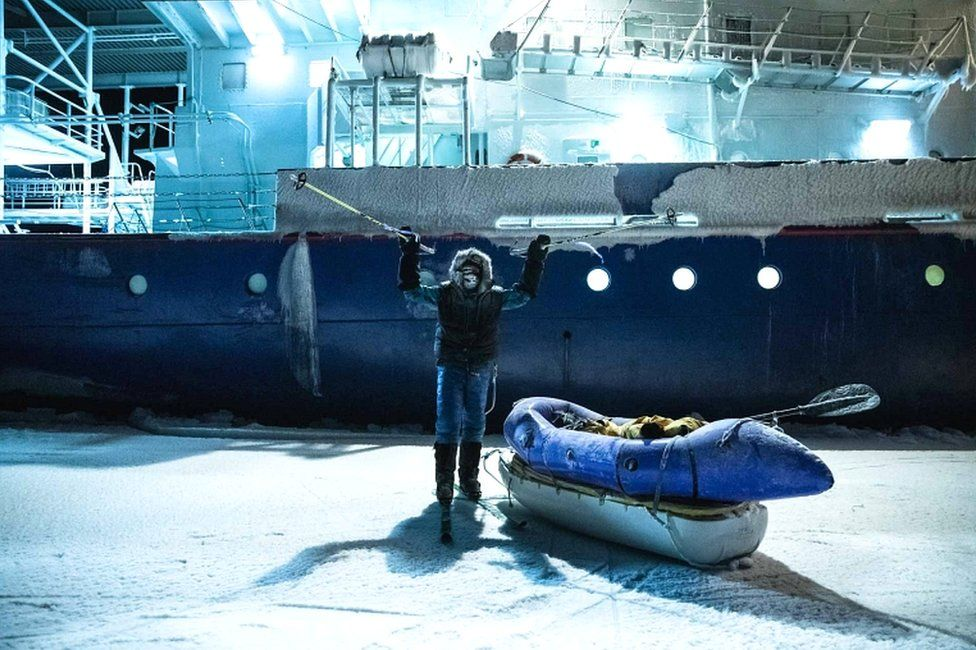 Picture handed out by the Mike Horn Sarl shows South African-born Swiss Mike Horn raising his ski sticks as he poses on 8 December 2019 in front of the Lance icebreaker boat in Norwegian waters of the Arctic Ocean