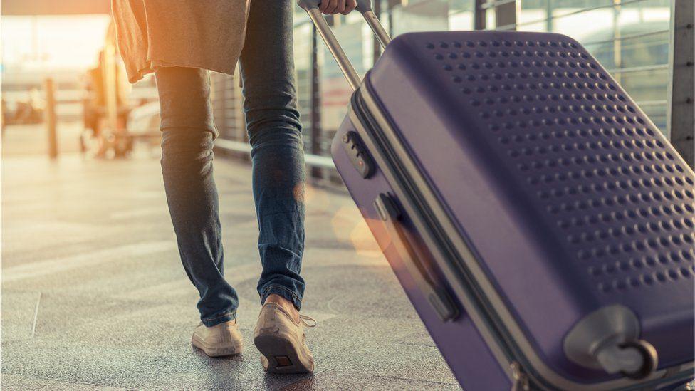 Man pulling suitcase through airport