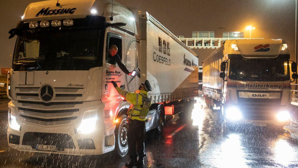 A police officer checks a lorry driver's phone at Dover Port, Kent, on Tuesday evening