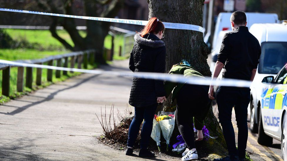 People laying flowers at the crime scene