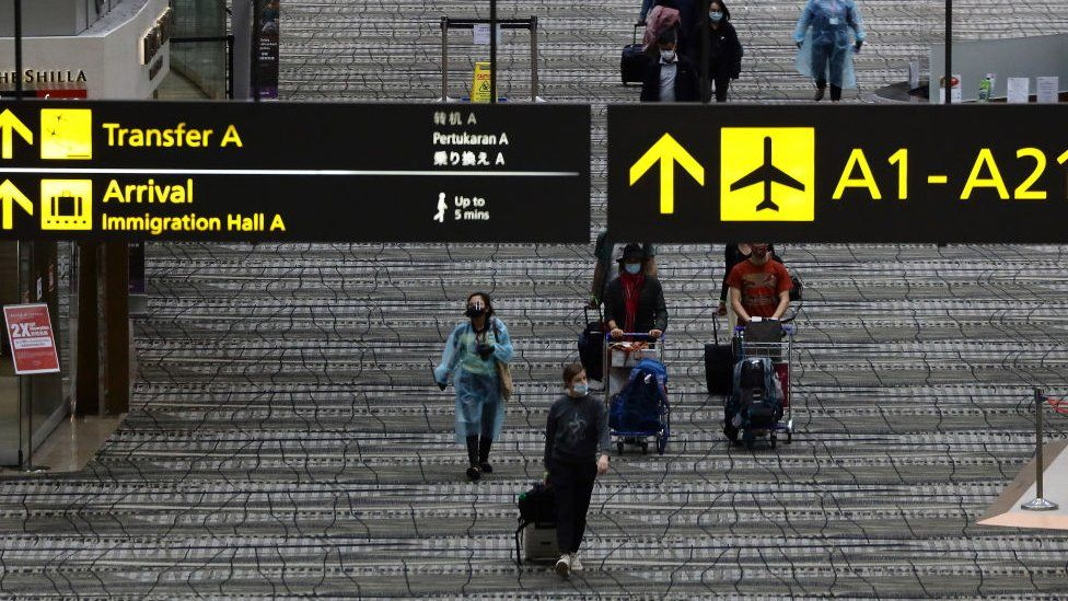 Travellers wearing protective mask walk along the transit area of Changi International Airport terminal on December 15, 2020 in Singapore.