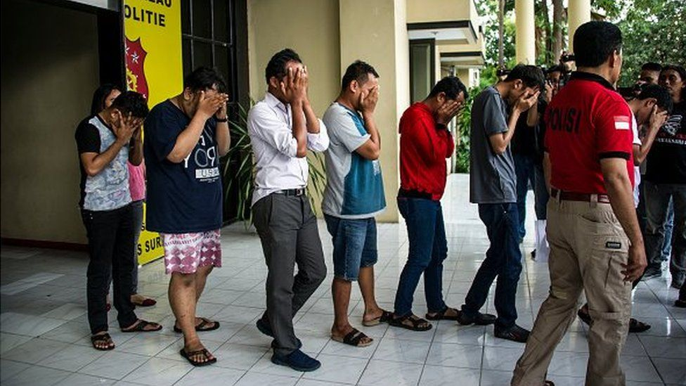 This photo taken on April 30, 2017 shows Indonesian police parading a group of men arrested for allegedly holding a 'gay party' in Surabaya, the second biggest city in Indonesia, the world's most populous Muslim-majority country. Officers busted 14 men holding the party in two hotel rooms in Surabaya, around midnight on April 29.