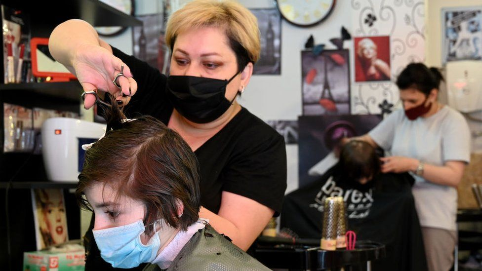 A hairdresser wearing a face mask cuts the hair of a client at a hairdressing salon in Georgia