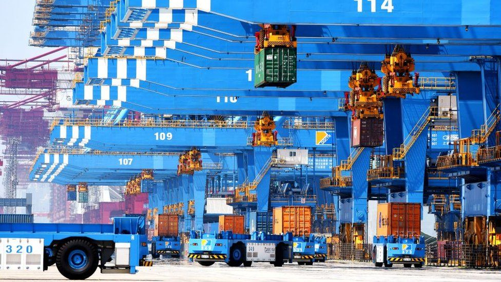 Auto-transporters and cranes move containers on a dockyard of a port in Qingdao in east China