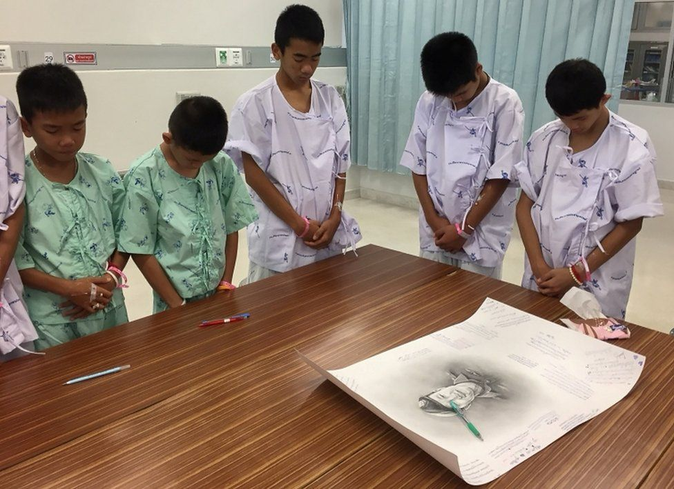 The young footballers bow their heads in commemoration after writing messages on a drawing of Samarn Gunan