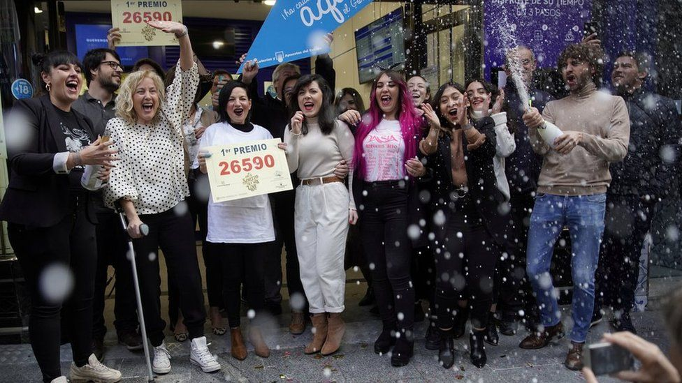 """Owners and employees of the shop """"Dona Manolita"""" celebrate selling the winning ticket."""