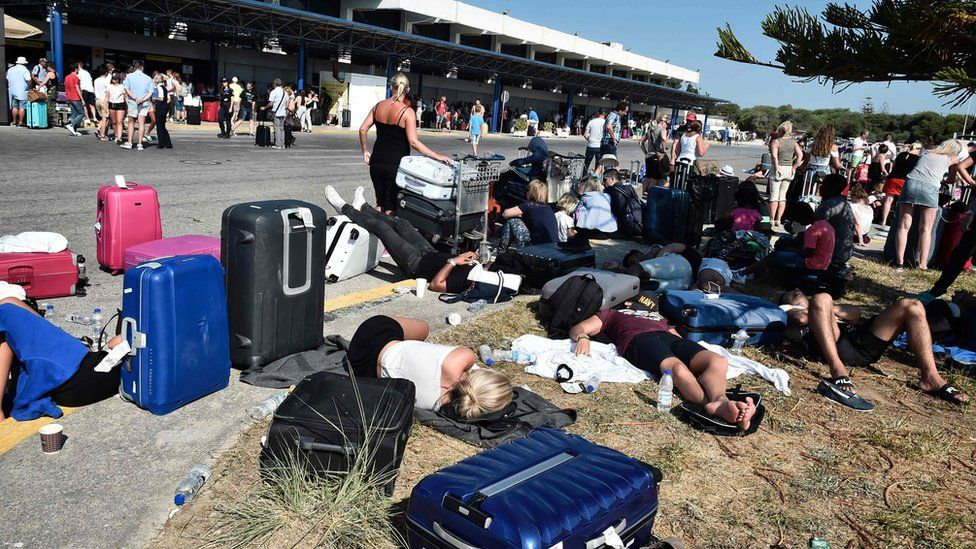 Tourists gather outside terminal buildings at an airport on the island of Kos following an earthquake, 21 July 2017