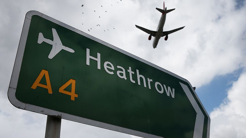 Plane flies over a road sign for Heathrow Airport