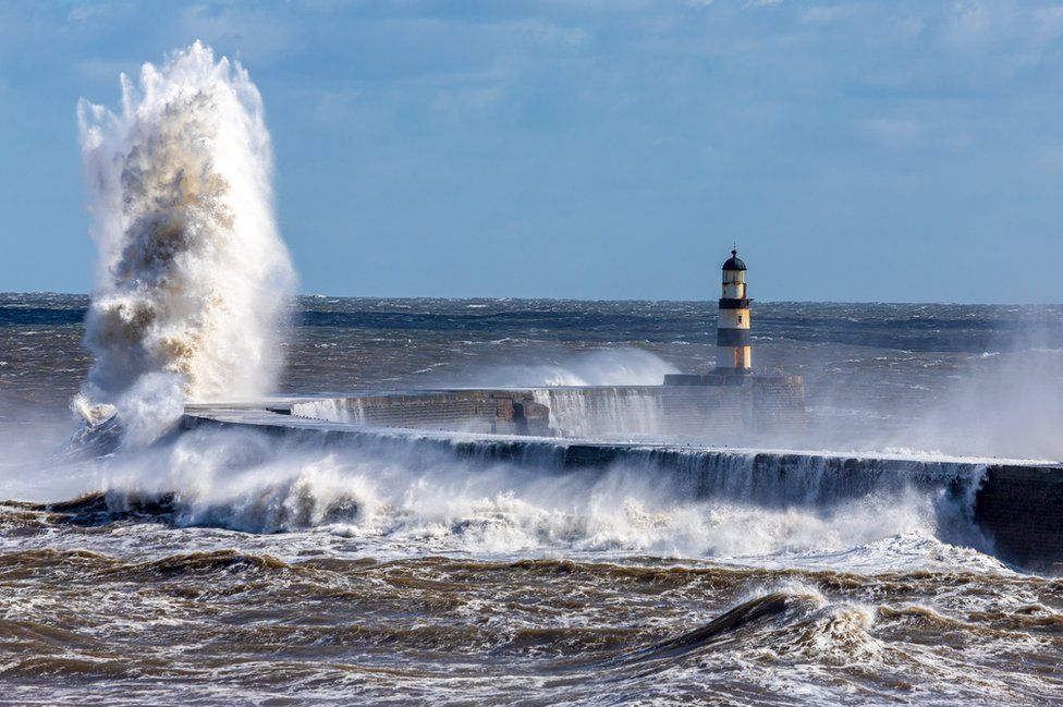 A large wave by a lighthouse