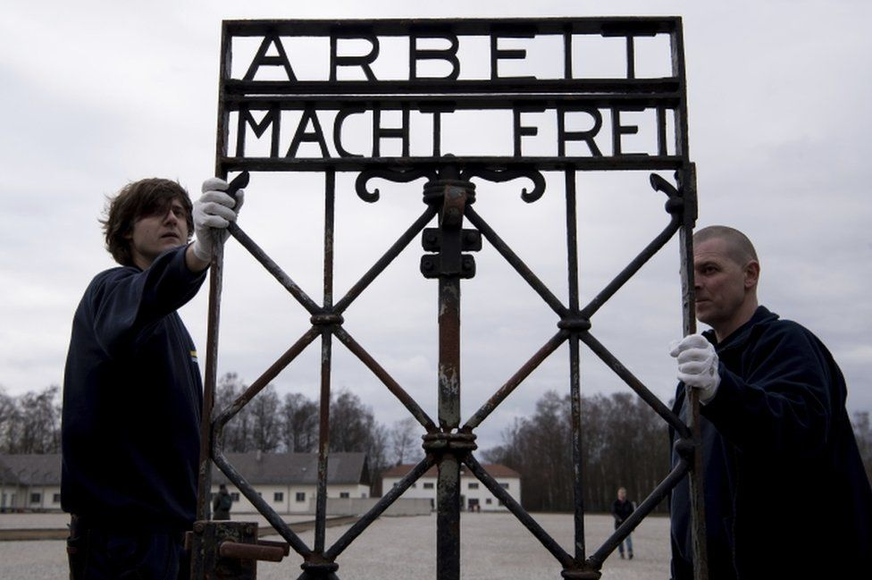 "Transport company staff carry the ""Arbeit macht frei"" gate at the site of the former Nazi concentration camp in Dachau on 22 February, 2017."
