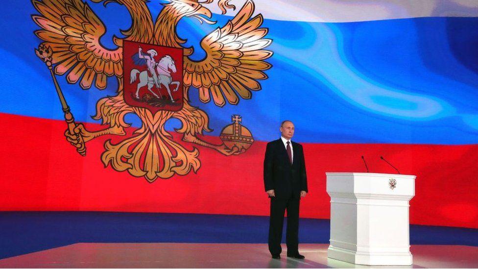 Vladimir Putin stands on stage during annual address