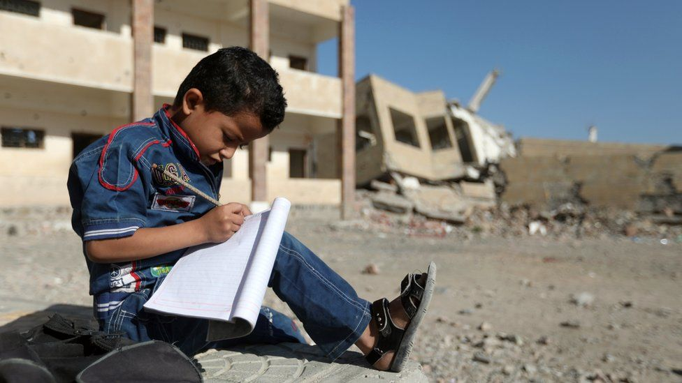 A Yemeni boy school writes as he sits outside a school which was damaged in an air strike in the southern Yemeni city of Taiz