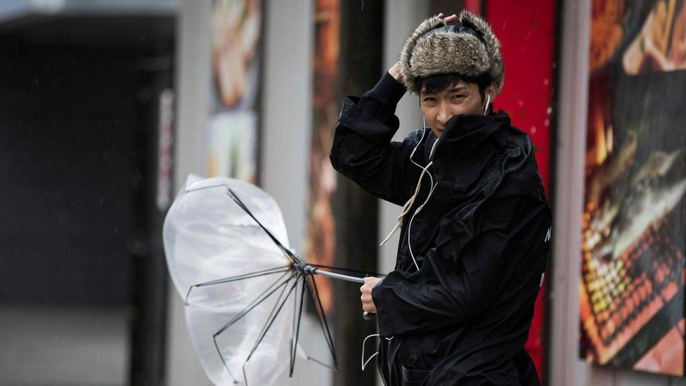 A pedestrian holds his broken umbrella on Japan's Kyushu island, 30 September 2018