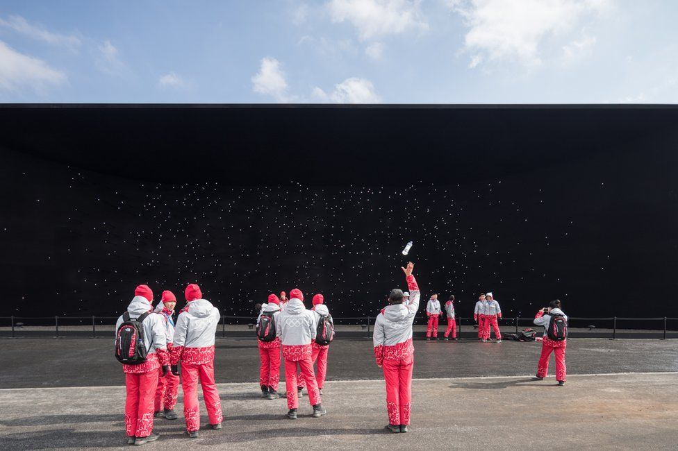 A group of tourists standing in front of a black wall