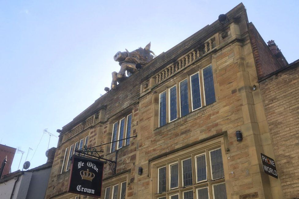 The boar's head on top of Ye Olde Crown pub