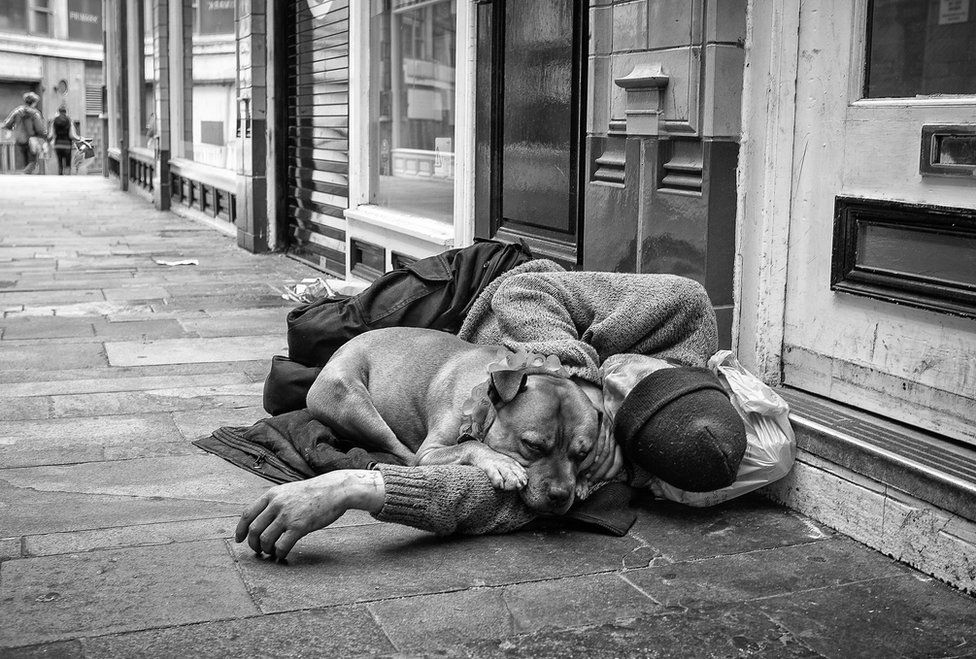 A homeless man sleeps with his dog in Birmingham City Centre.