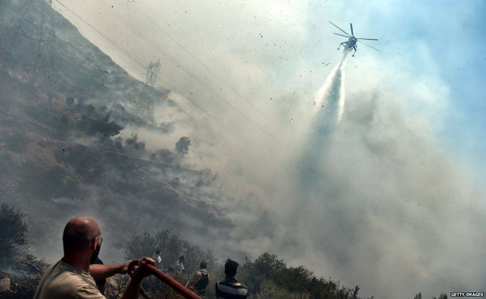 A fire fighting helicopter sprays water on a fire as residents look on, in Athens 17 July 2015