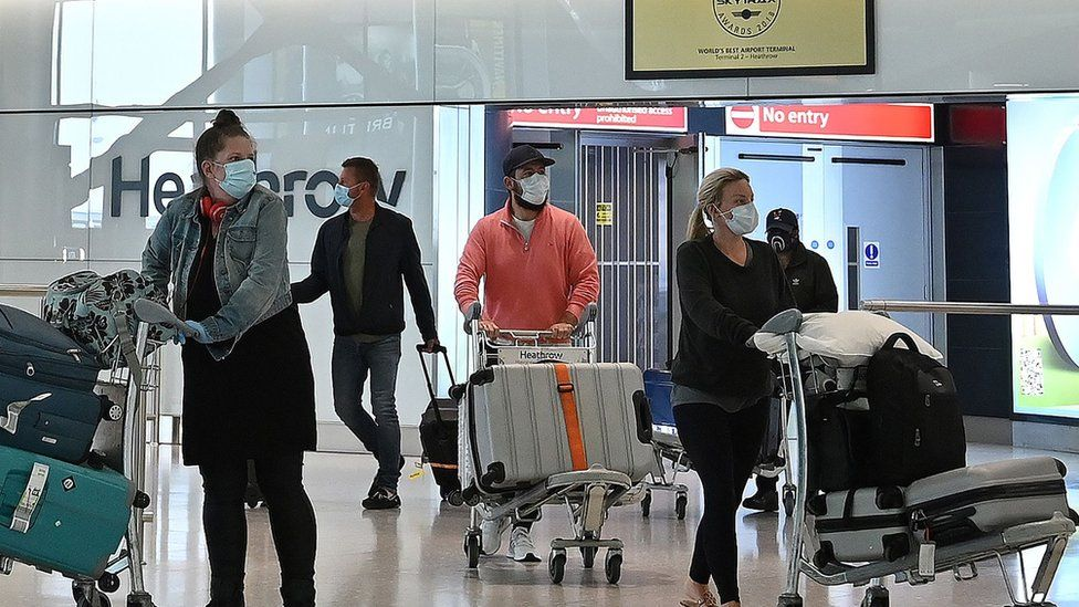 Travellers wearing masks arrive at Heathrow Airport