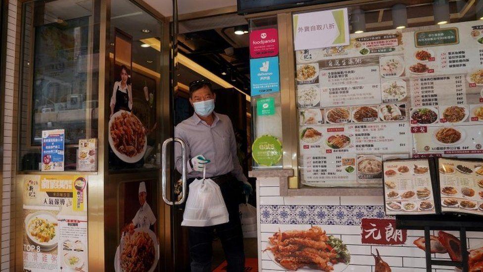 A man gets a takeaway from a Hong Kong restaurant