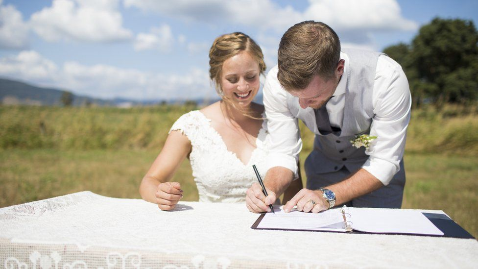 A couple signing a marriage register