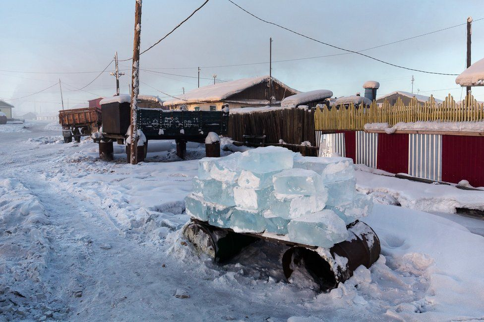 To ensure the village's water consumption, men cut blocks of ice into the river and deliver them to the inhabitants. Each house has its own stock of water stored outside in stacks of ice blocks.