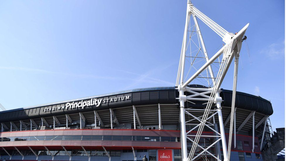 The Principality Stadium with an abseiling cleaner