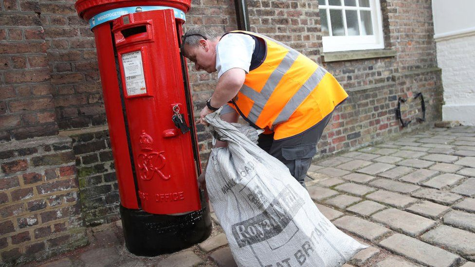 Postman empties letter box