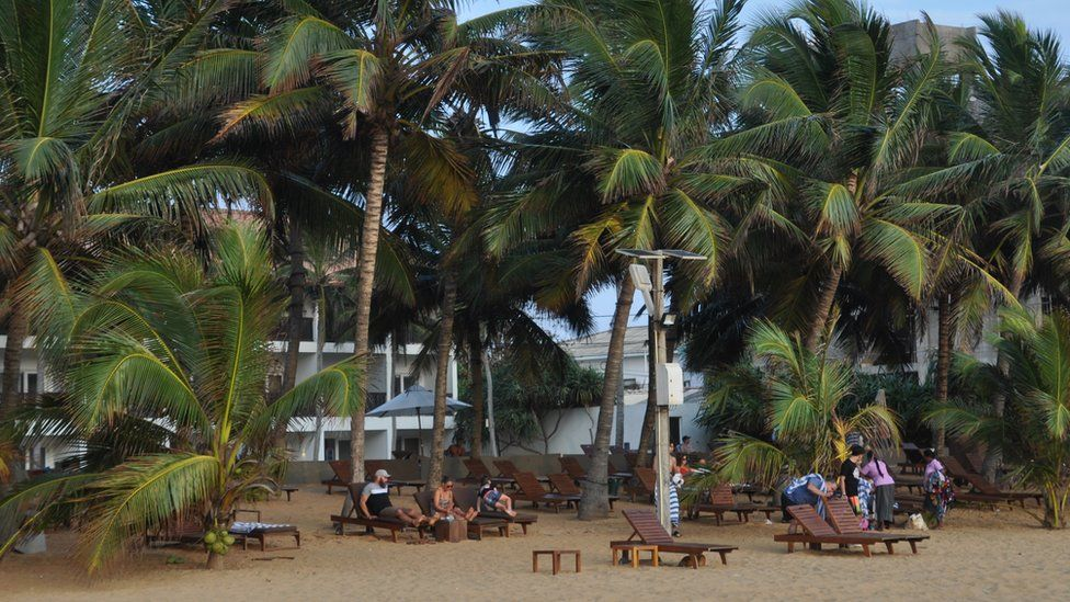 Tourists sit on the beach in Sri Lanka