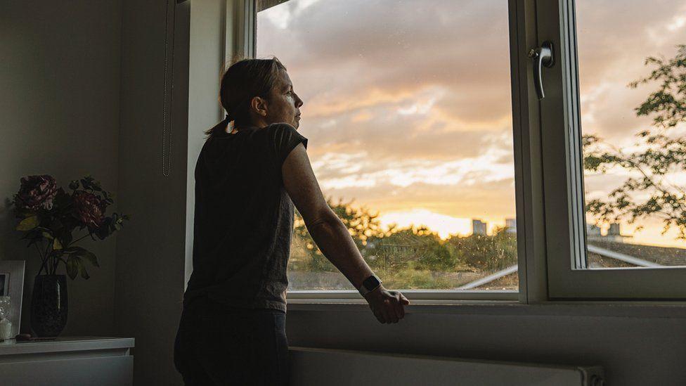 Woman looks through window