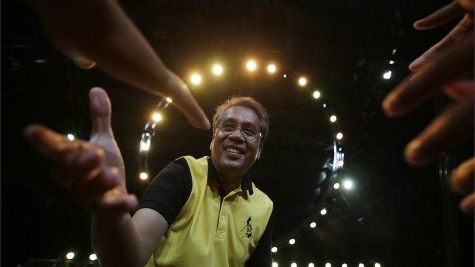 Mar Roxas, former Interior and Local government secretary and now a presidential candidate reaches out to greet supporters during a campaign sortie in suburban Quezon city, north of Manila
