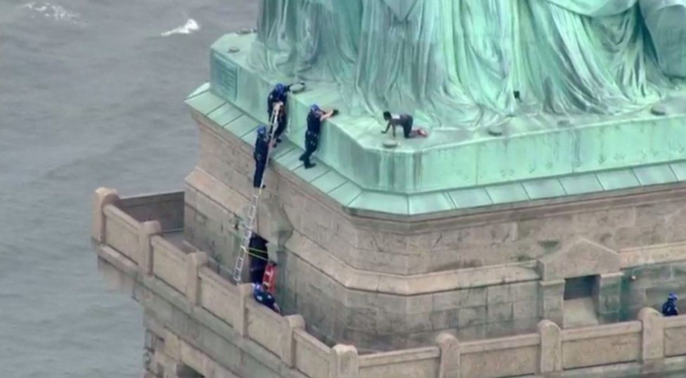 A screengrab shows police talking to a woman who climbed to the base of the Statue of Liberty in New York