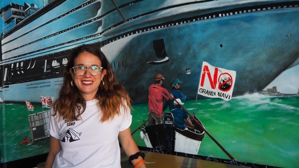 Environmental activist Sofia Demasi in front of a mural of a cruise ship and a small boat with a 'No Big ships' logo