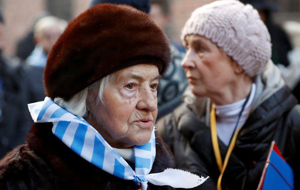 Holocaust survivors walk through the grounds of former German Nazi death camp Auschwitz