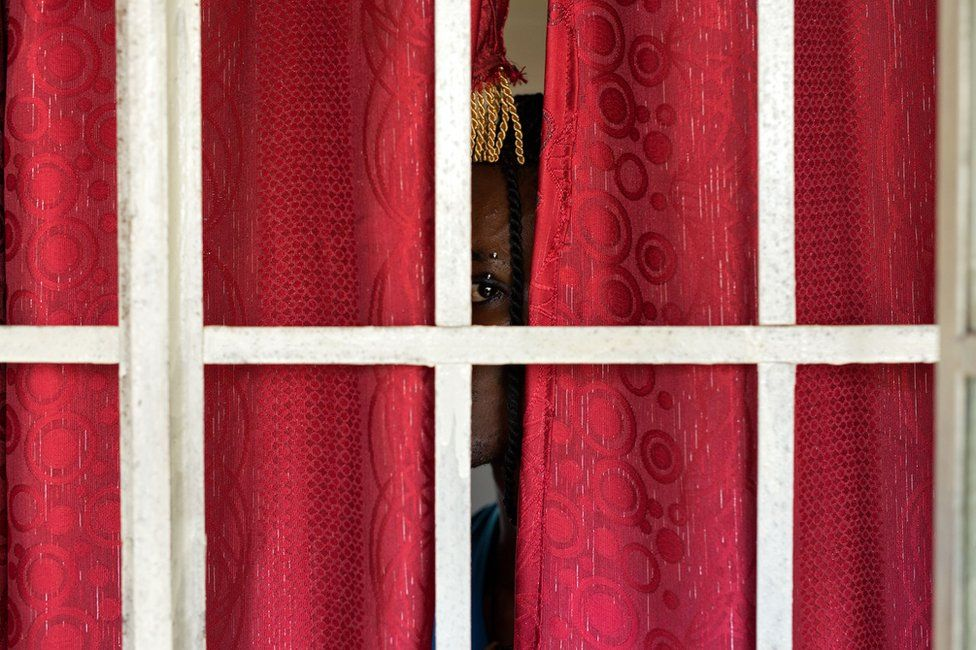 Person peeking through a pair of closed red curtains