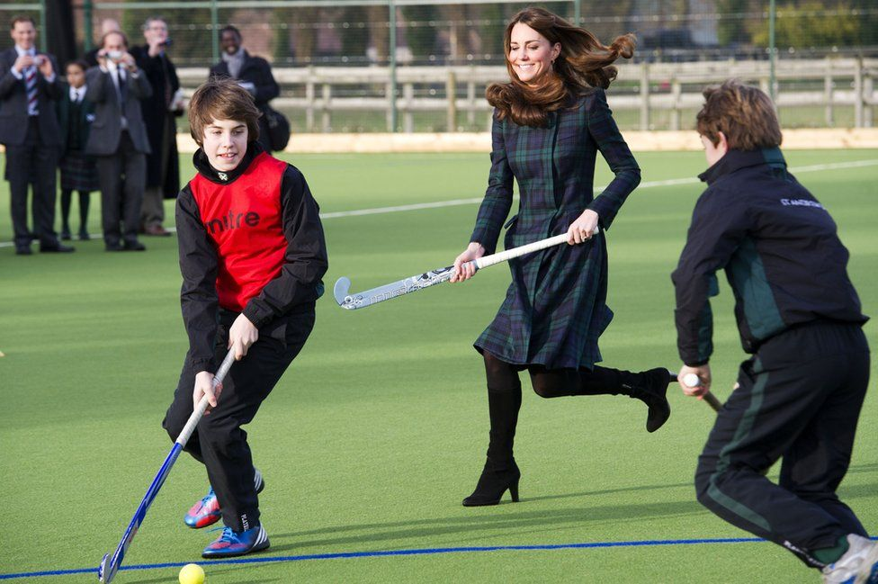 Catherine, Duchess of Cambridge plays field hockey in a coat and heels at St Andrew's School on November 30, 2012
