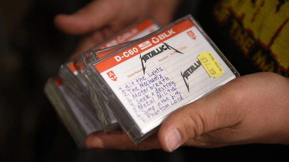 An employee of a music shop holds copies of Metallica's reissued 1982 demo tape in 2015