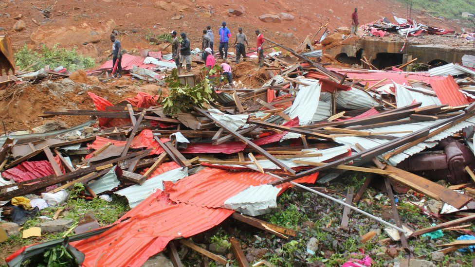 People inspect the damage after a mudslide in the mountain town of Regent, Sierra Leone August 14, 2017