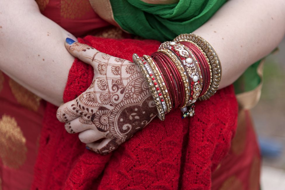 Sikh woman with henna-patterned hands