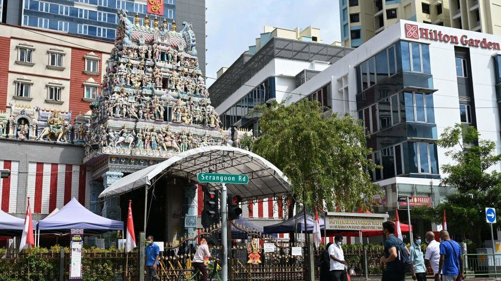 Pedestrians cross the road in front of the Sri Veeramakaliamman temple in the district of Little India in Singapore on September 15,