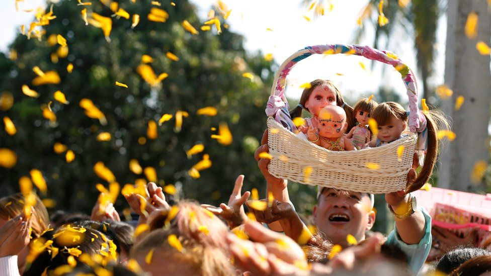 A man holds up a basket of the dolls at a religious event for them