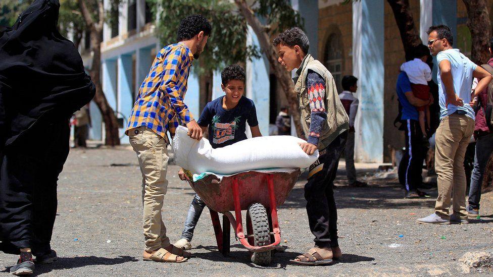Yemenis receive humanitarian aid provided by the World Food Programme (WFP) in the Yemeni capital Sanaa
