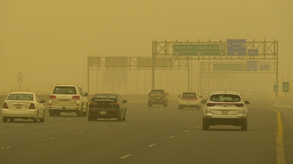 Vehicles transit at a road shrouded in heavy dust in Kuwait City, Kuwait, 13 June 2021