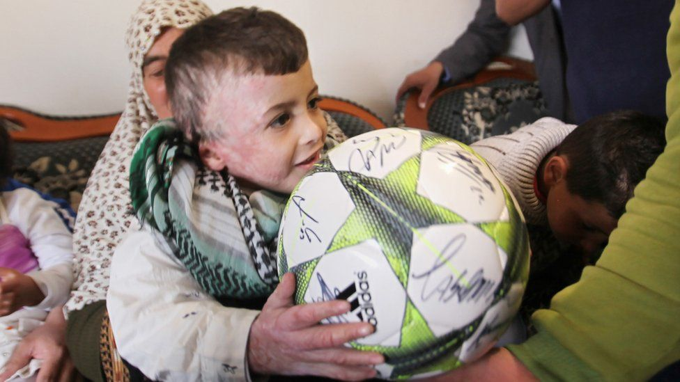 Ahmed Dawabsha holds a football while visiting his relatives in 2016